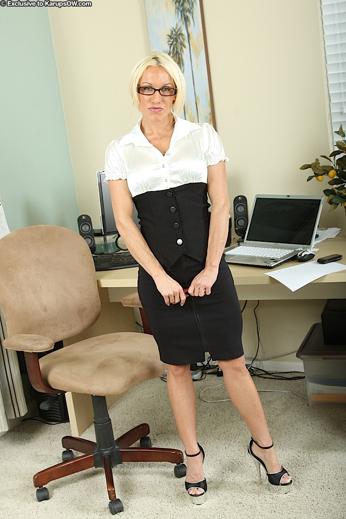 Lustful mature blonde in dress clothes revealing her goods in her office