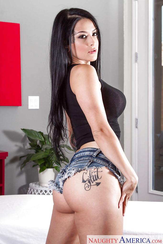 Beautiful brunette Katrina Jade poses on deb in short denim shorts