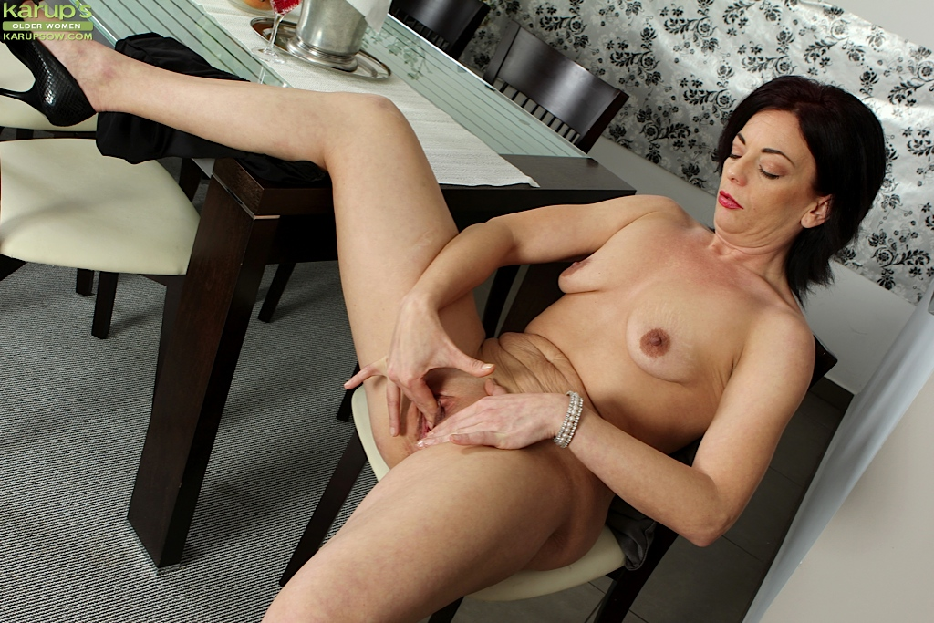 Mature woman enjoying on the couch by massaging her pussy