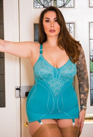 Fat woman Paige Turnah cups a breast in lingerie paired with tan nylons