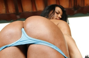Busty Brazilian chick Nanda Paiva models her oiled body beside pool