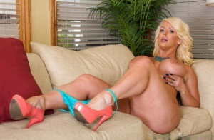 Extremely busty blonde mommy Alura Jenson bending over on a couch
