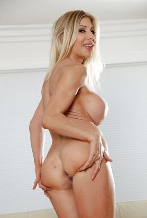 Buxom blonde MILF Puma Swede exposing huge breasts while posing in spandex