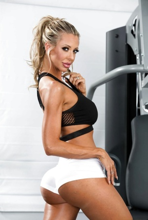 Sporty blonde MILF gets naked in the gym to masturbates her hairless pussy