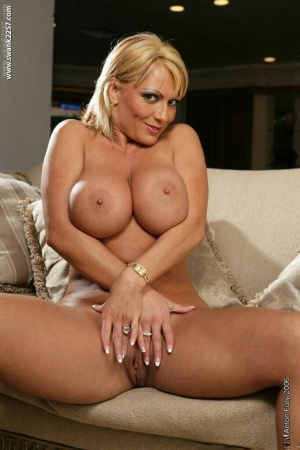 Well-stacked blonde MILF undressing and caressing herself
