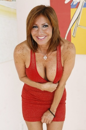 Redheaded American MILF Tera Holiday frees her girl parts from a red dress