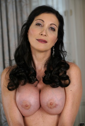 Mature woman Sissy Neri shows her silicone tits and slender body in stockings