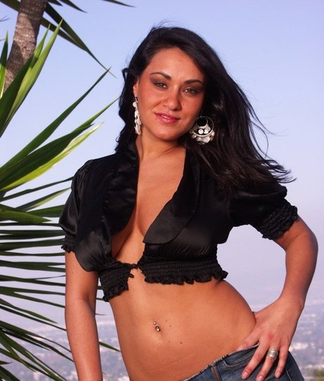 Latina model Charley Chase unleashes her natural tits as she strips to boots