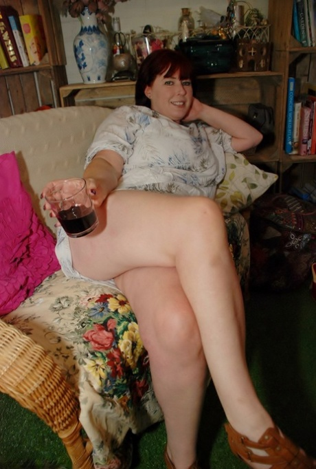 Redhead amateur BBW smokes while sliding cutoff shorts aside on a couch