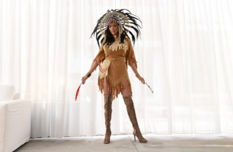 Mature woman in Native American attire has her big tits and twat fondled