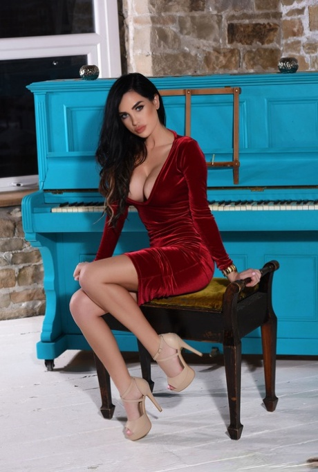 Dark haired Ann Denise in red dress flashes sexy upskirt and flaunts big tits
