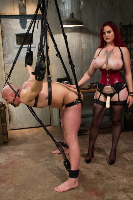 Busty redheaded femdom Mz Berlin whipping her bald tied up male slave's ass
